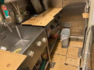 ネズミ駆除用粘着シートを厨房内ガス台に敷く